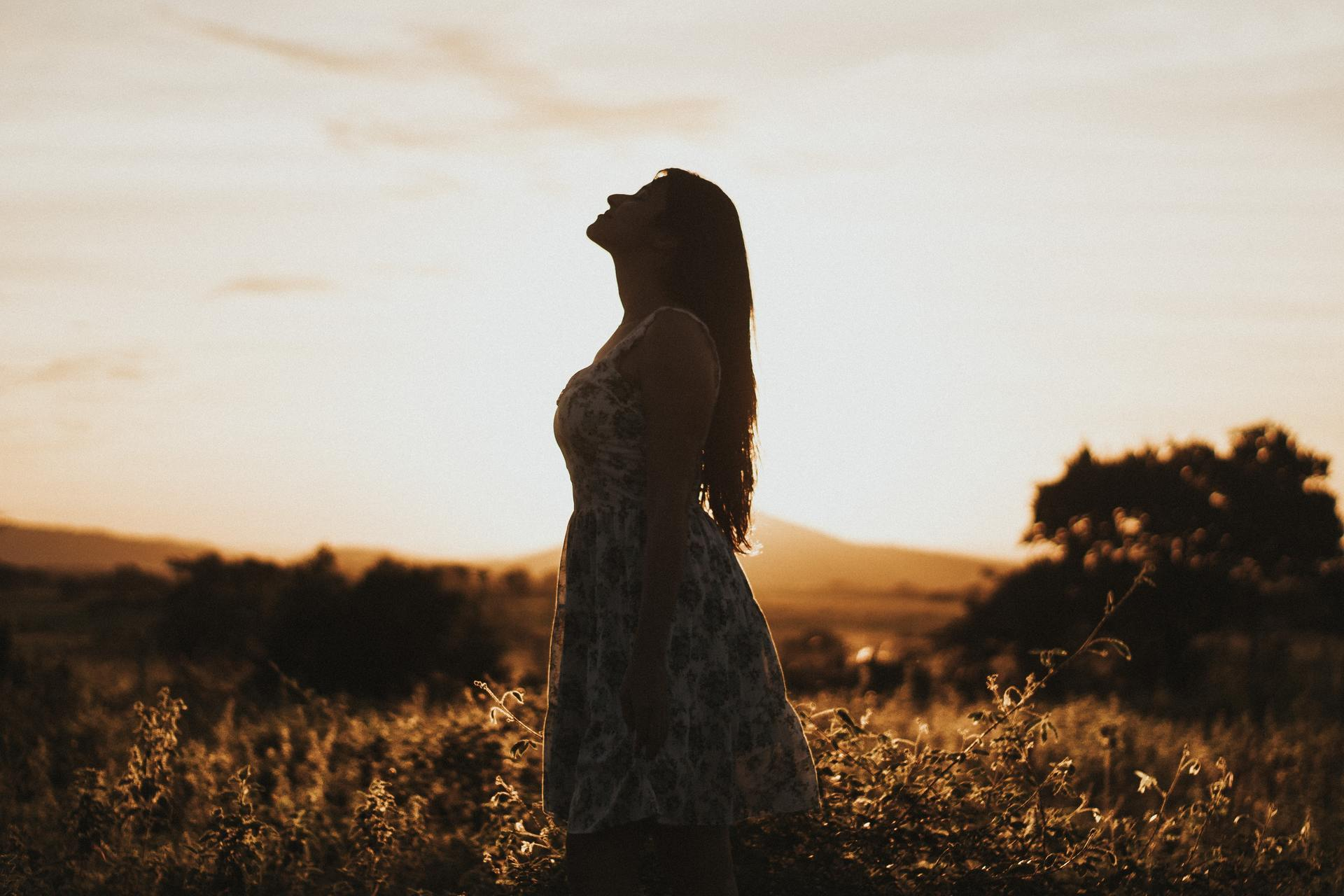photo-of-woman-standing-in-field-during-dawn-2810209.jpg